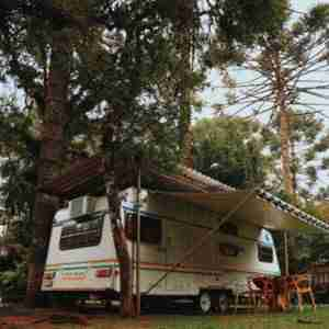 RV parked under tall trees. A Girard tankless water heater will provide long hot showers wherever the water supply is available.
