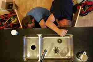Plumbers installing a new garbage disposal in Las Vegas.